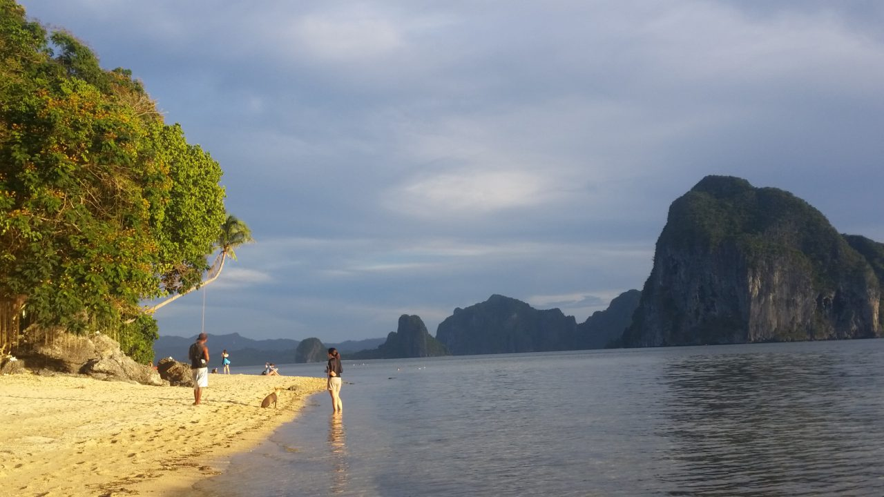 Beach in afternoon sunlight with tourists near El Nido