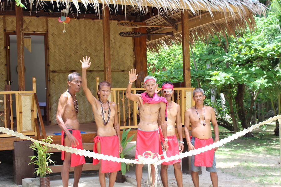 Tribal people in front of a hut